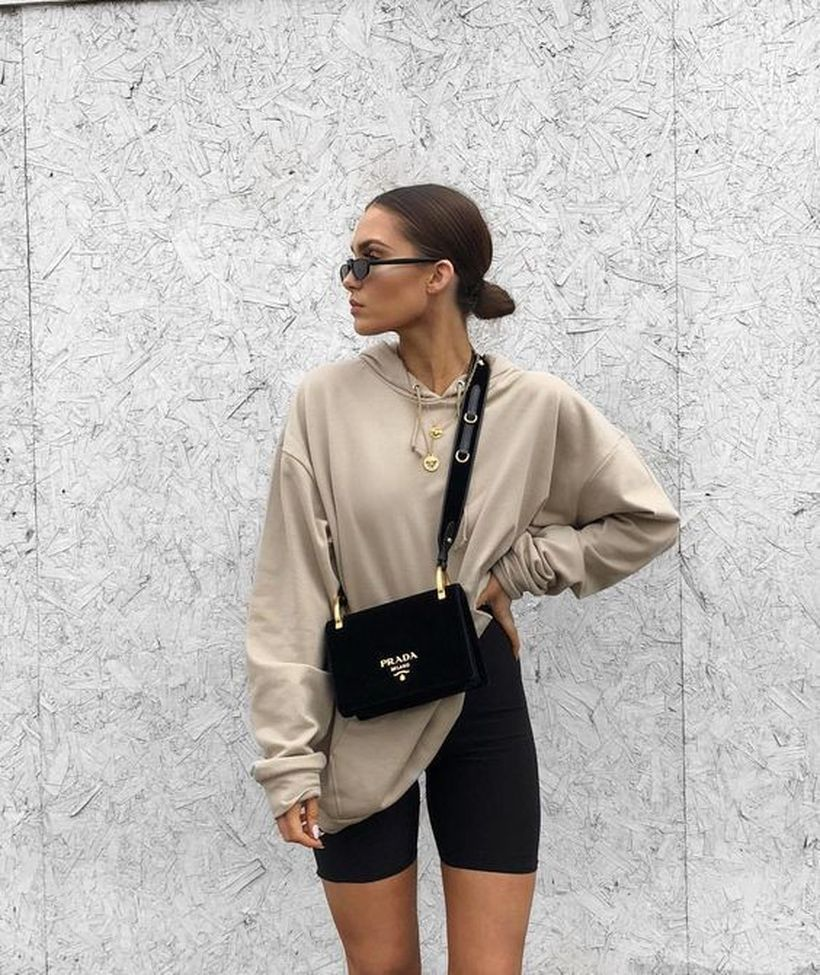 A-fabulous-wear-bike-outfit-combined-with-a-white-oversized-hoodie-black-bike-shorts-white-trainers-and-a-small-black-bag.-1-1