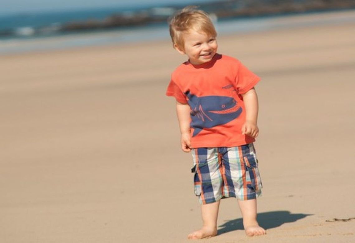 Summer-clothing-brands-for-boys-with-shark-pattern-on-orange-t-shirt-and-plaid-shorts-pocket-beside