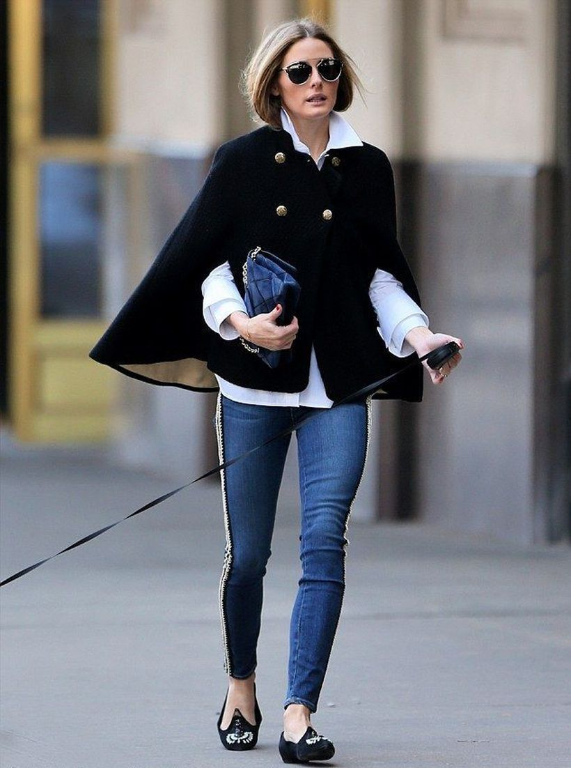 An amazing outfit with black cape blazer button, white shirt, blue denim pants and black flat shoes for street style