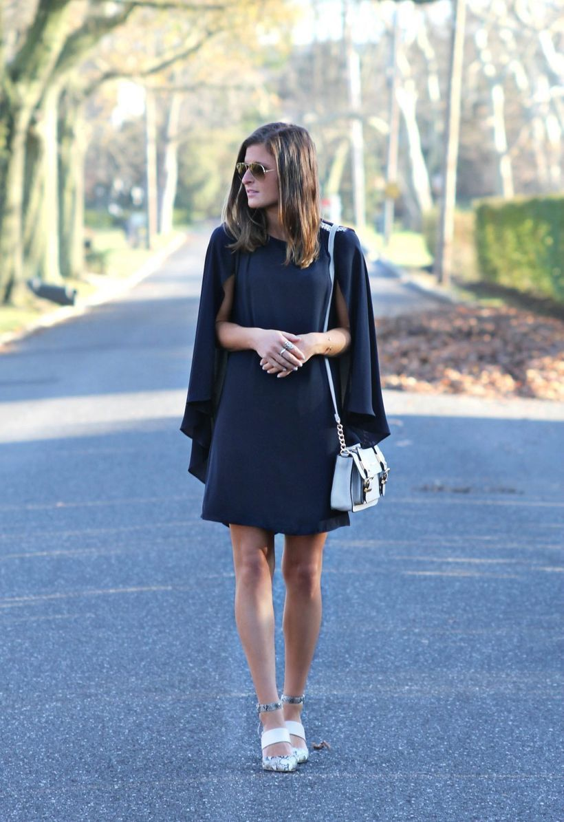 Stunning mini black cape dress with white shoes and glasses to look wonderful