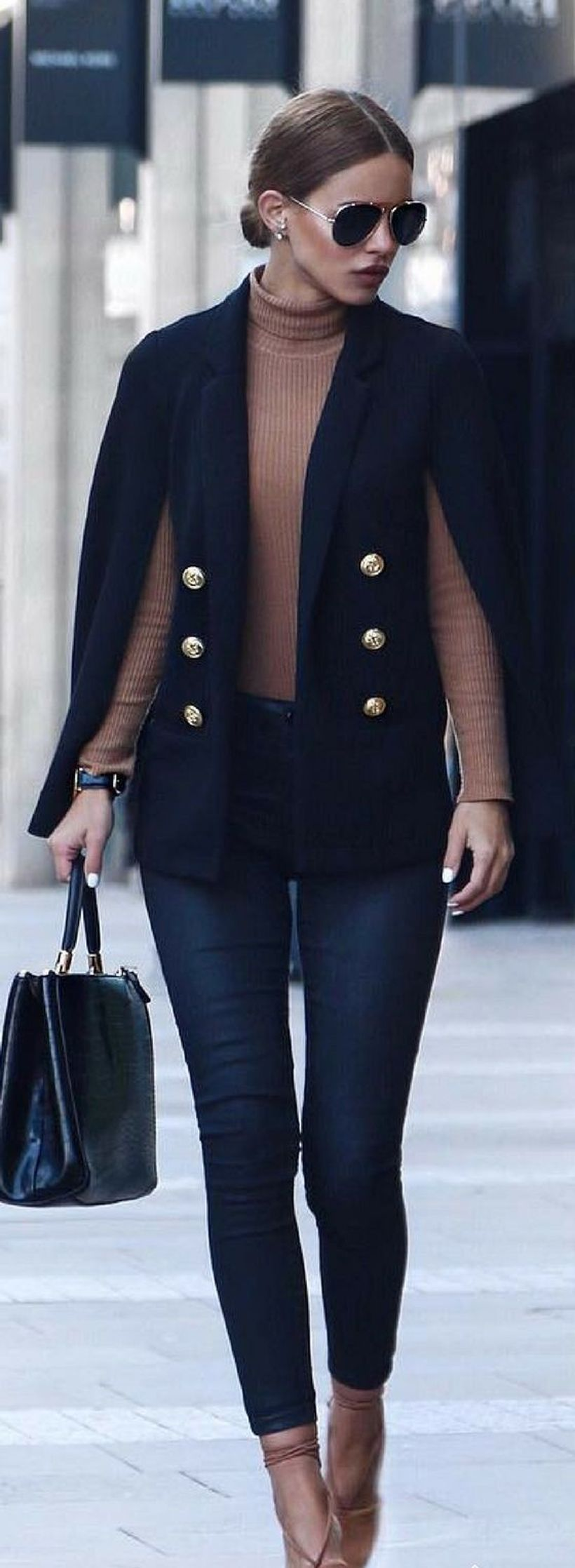 Elegant outfit with black cape blazer button, brown sweater, dark blue denim pants and beige high heels