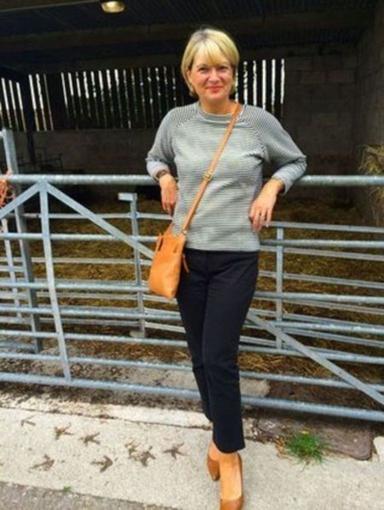 Light grey top combined with black pants and sling bag